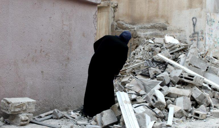 Moteris apžiūri Izraelio kariuomenės sugriautą šeimos namą Kalandijos tremtinių gyvenvietėje.