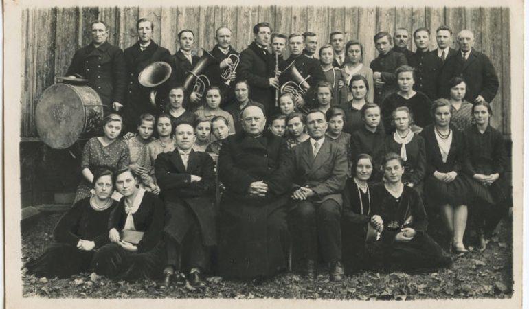 Burbiškių kaimo muzikantai ir Gaurės katalikų bažnytinis choras (Tauragės apskr.) 1936 metais prie Gaurės bažnyčios. Per vidurį sėdi klebonas kanauninkas Kazimieras Šleivys. Nuotrauka iš Albino Batavičiaus archyvo.