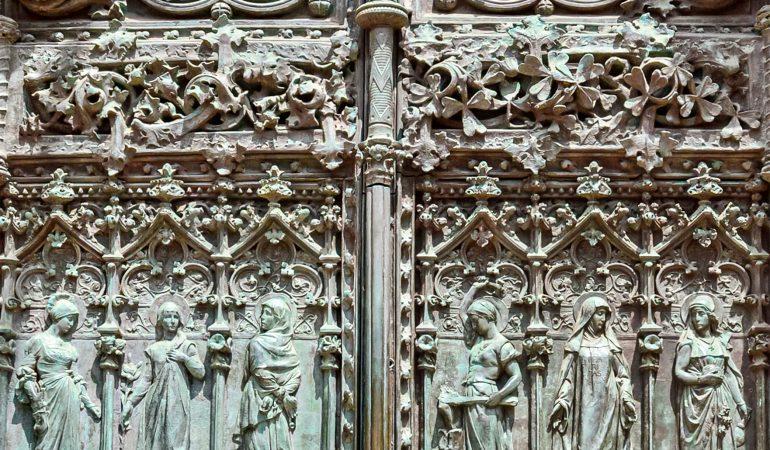Dorybių durys: šešios dorybės, pamynusios joms priešingas ydas simbolizuojančius gyvūnus; jas vainikuoja nuolankumo dorybė: apreiškimą priimanti pati Mergelė Marija. O kurgi jai priešinga yda – puikybė? Ją vaizduoja... visos šios prabangios dvitonės bronzinės durys. Senasis jėzuitų universiteto pastatas. Luis Domenechi Montaner, 1890, Camillas, Ispanija. J.Micevičiūtės nuotrauka.